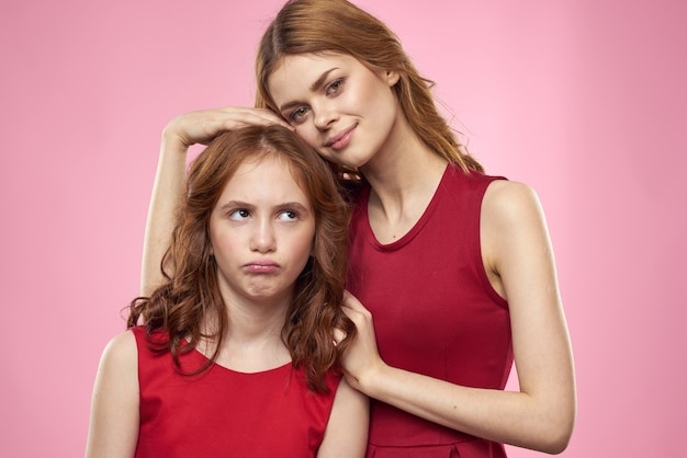 ママと娘の楽しいコミュニケーション家族の喜びピンクの背景のトリミングされたビュー