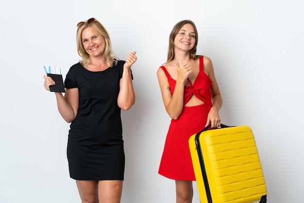 ママと娘は白い壁に孤立して旅行に行く両手で親指を立てるジェスチャーを与え、笑顔