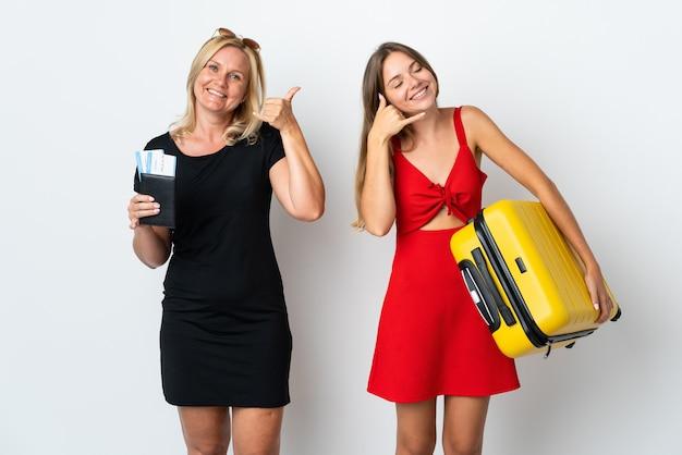 電話のジェスチャーを作る白い壁に孤立して旅行に行くママと娘。コールバックサイン
