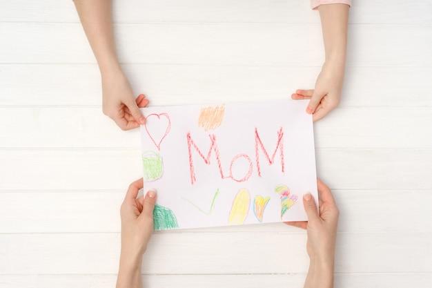 Мама и дочь руки держат красочные открытки diy со словом мама написано на нем. милая открытка ручной работы на день матери или 8 марта на день рождения