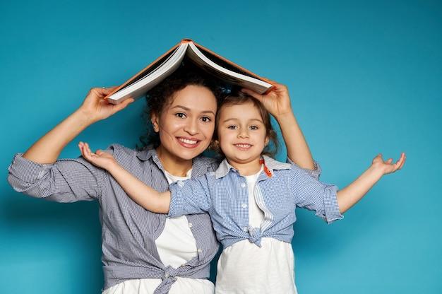 엄마와 딸이 집에서 지붕 형태의 오렌지색 책을 머리 위로 들고 정면에서 행복하게 미소 짓습니다.