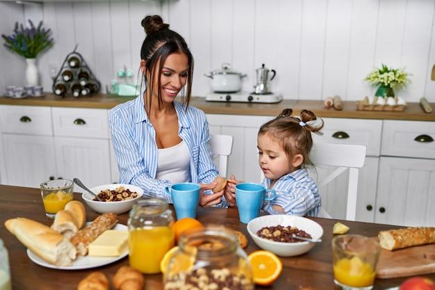 ママと娘は家で朝の朝食を持っています。
