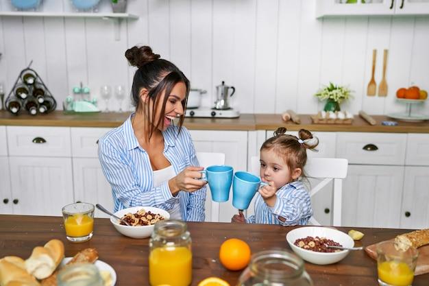 ママと娘は家で朝朝食をとる