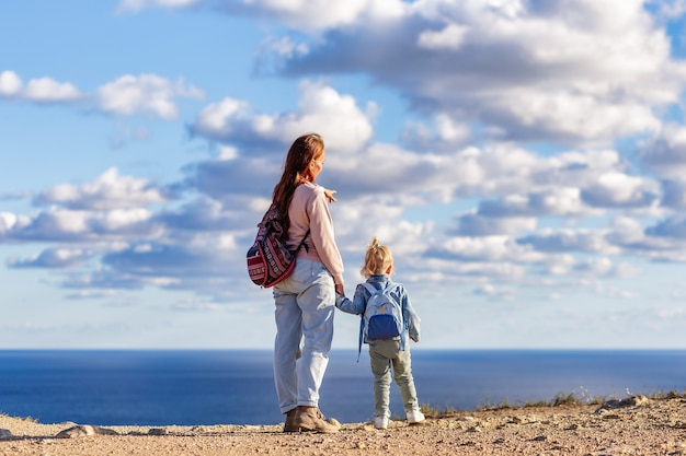 Мама и дочь поднялись на гору и смотрят на море спиной к камере.