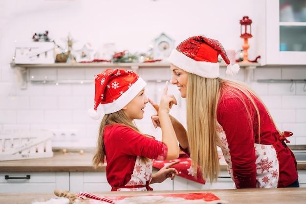 Мама и дочка веселятся на кухне и смеются в новогодних шапках.