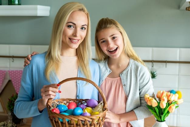 엄마와 딸 부활절 달걀 바구니를 들고.
