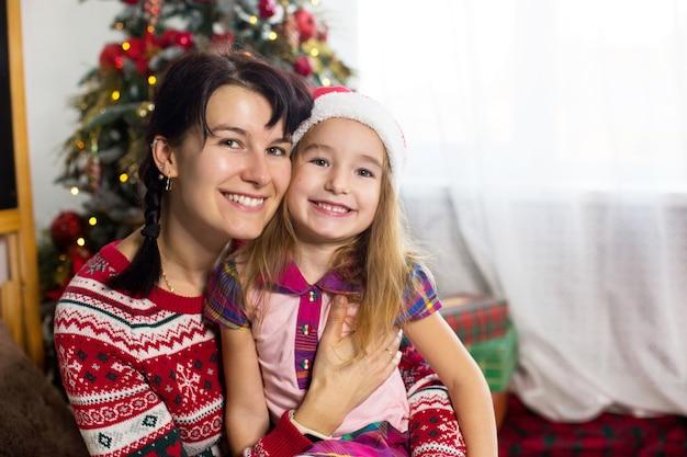 ママと娘が抱きしめ、幸せそうに笑って、クリスマスツリーの近くに家に座って