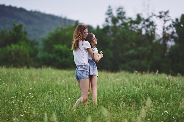 花のフィールドでママと娘が楽しい休暇の子供時代を歩く
