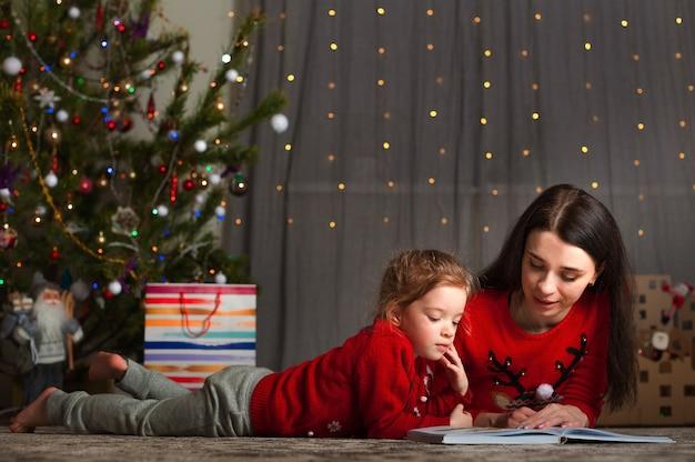 クリスマスツリーでクリスマスの赤いセーターのママと娘。休暇中は家にいてください。