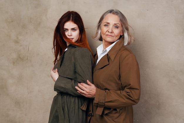 ライフスタイルをポーズする秋のコートファッションのママと娘