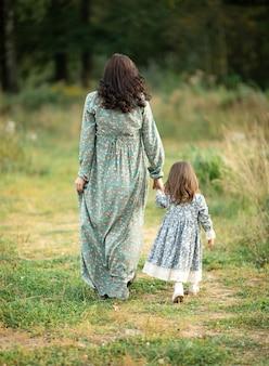 엄마와 딸이 아름다운 빈티지 드레스를 입고 자연 속에서 산책