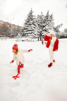 Мама и дочь в красивой зимней одежде играют в снежки в зимнем парке. семейный взгляд