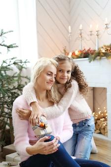 クリスマスに装飾されたリビングルームでの母と娘