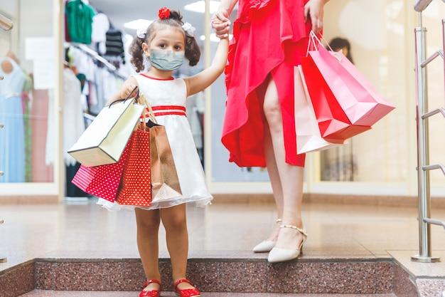 色付きのバッグとモールでドレスを着たママと娘。顔の医療用マスクで