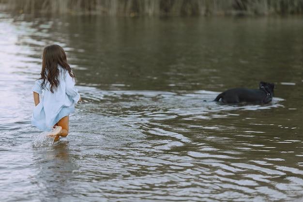 Мама и дочь в одинаковых платьях. семья играет у реки.