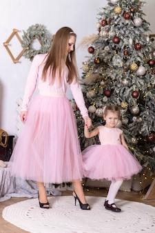 Мама и дочка в одинаковых розовых платьях из тюля радуются возле елки