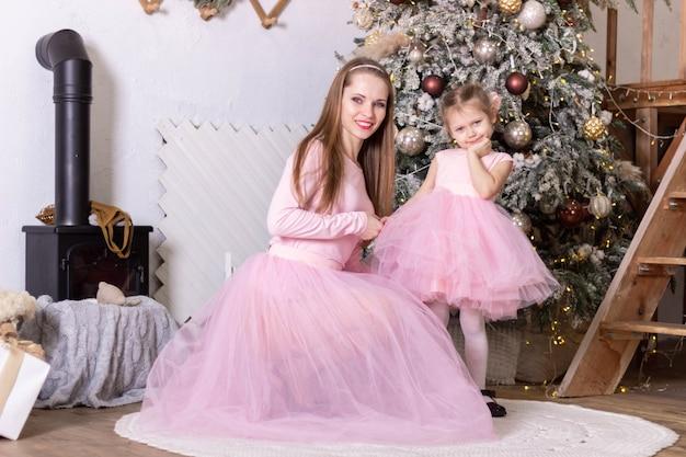 Мама и дочка в одинаковых розовых платьях из тюля держатся за руки возле елки