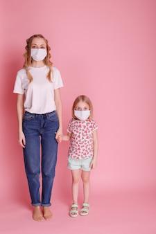 엄마와 딸이 분홍색 표면에 얼굴에 의료 마스크