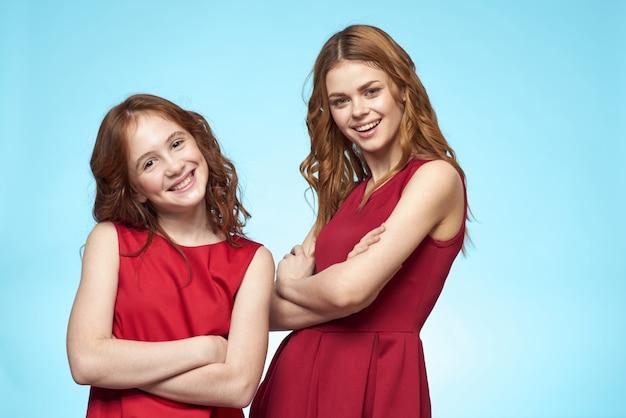 赤いドレスを着たお母さんと娘は、エンターテイメント ライフスタイルの楽しいスタジオの青い背景を着ています。高品質の写真