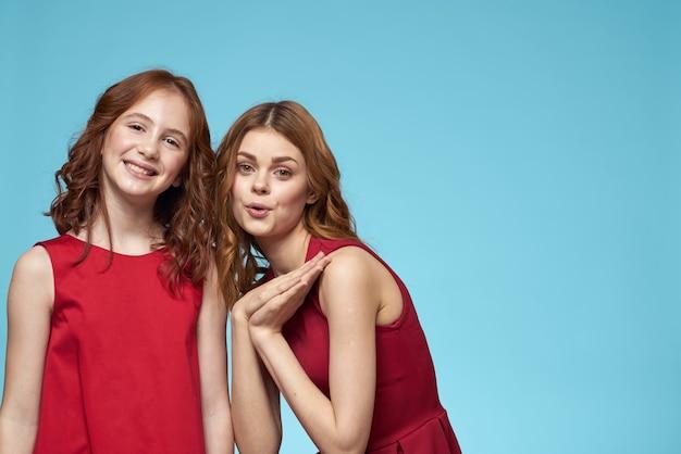 赤いドレスのママと娘エンターテインメントライフスタイル楽しいスタジオ青い背景