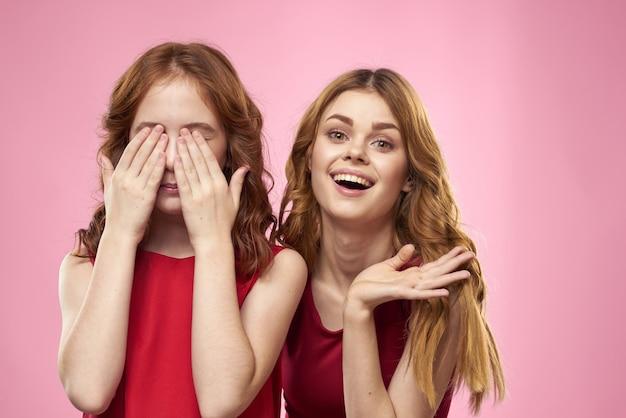 赤いドレスを着たママと娘は楽しいしかめっ面子供時代の喜びピンクの背景を抱擁します