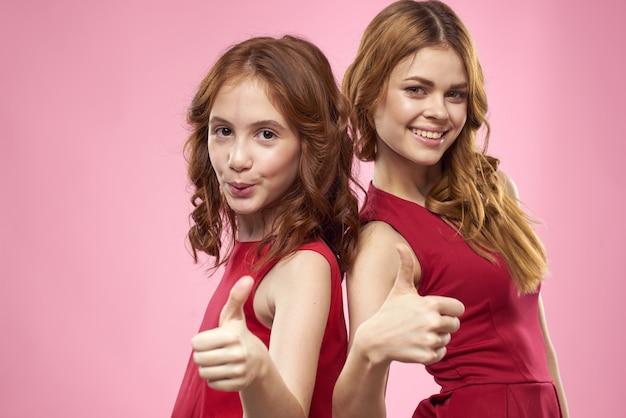 赤いドレスを着たママと娘が楽しいしかめっ面の子供時代の喜びのピンクを抱きしめます