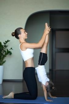 Мама и дочь в спортивной одежде выполняют упражнения, лежа на коврике