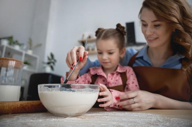 キッチンのママと娘は楽しんで、小麦粉のミルクと卵から食べ物を調理します
