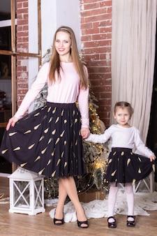 Мама и дочка в одинаковых юбочках и свитерах стоят возле елки