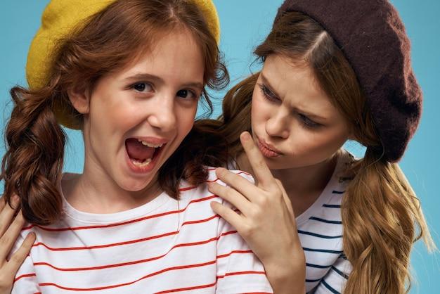 Мама и дочка в студии позируют веселиться и улыбаться, счастливая семья, две сестры, образ франции и парижа, берет на голову