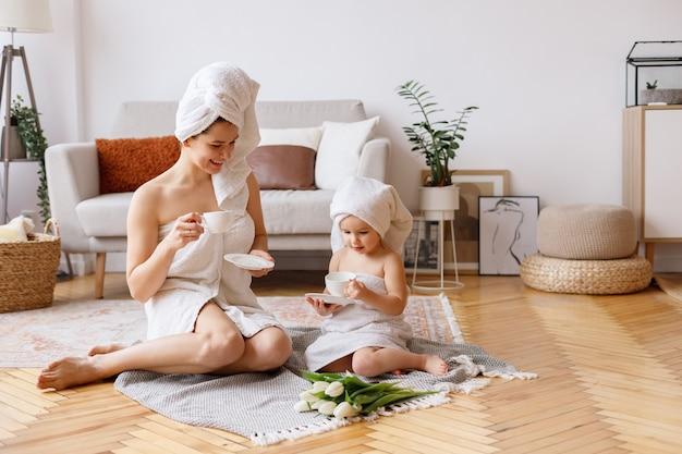 엄마와 딸이 거실에서 수건을 마시고 차를 마신다.