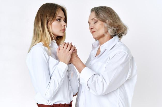 白いシャツを着たママと娘が家族の楽しいライフスタイルの隣に立っています