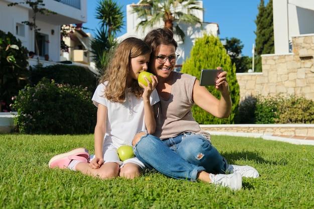 영상 통화를 위해 스마트폰을 사용하는 엄마와 딸 아이. 마당에 푸른 잔디에 앉아 가족