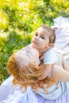 Мама и дочь смеются и обнимаются, сидя на одеяле в парке, концепция счастливой семьи ...