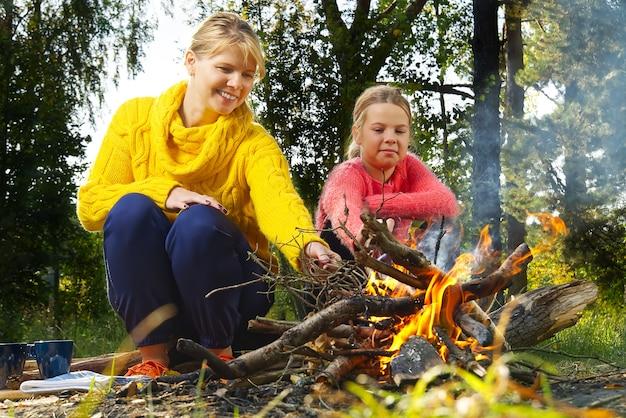 Мама и дочь зажигают костер в лесу