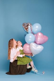 엄마와 딸이 풍선을보고 어머니의 날에 미소 짓는다.