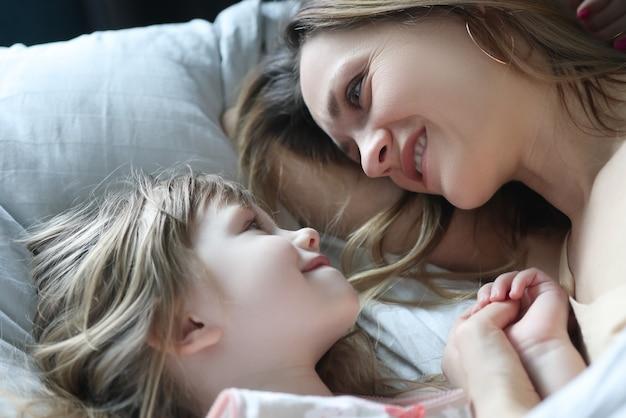 Мама и дочь смотрят друг на друга и лежат в постели