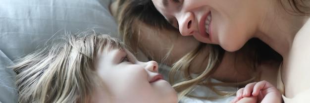 엄마와 딸이 서로 보고 침대에 누워