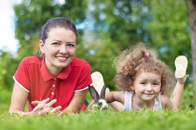 ウサギと緑の草の上に横たわっているママと娘。ペットと遊ぶ若い女性と少女。イースター、おめでとう