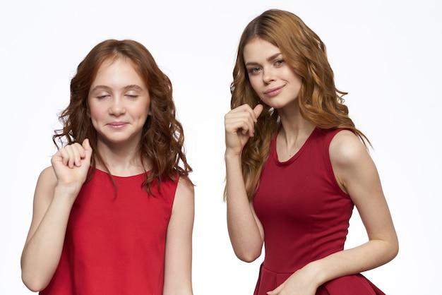 赤いドレスの横にあるママと娘がライフスタイルの明るい背景の笑顔を抱擁