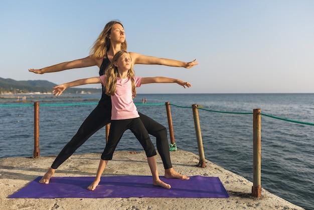 海沿いの桟橋で晴れた夏の夜にママと娘がvirabhadrasana運動を行います