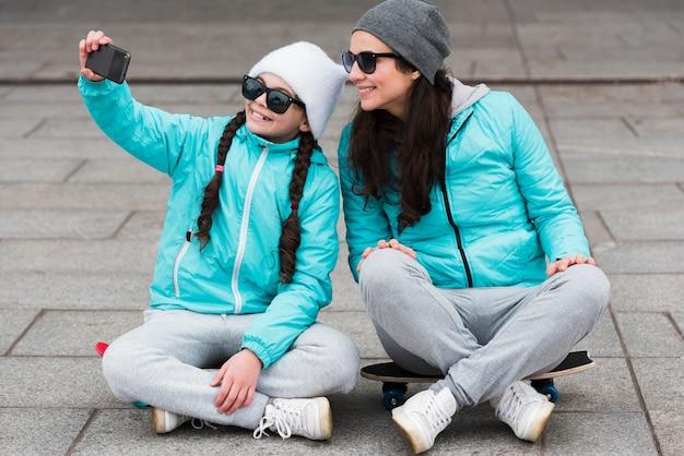 Мама и дочка на скейтборде принимая селфи
