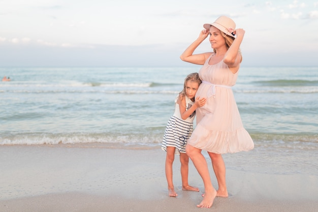 엄마와 딸이 저녁에 해변에서. 자연 부모 개념.