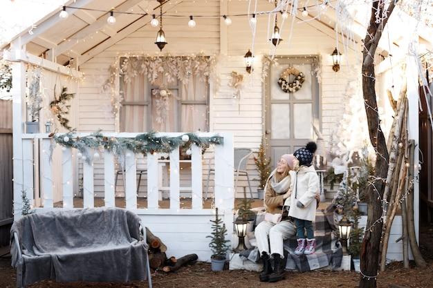 クリスマスの冬の家のベランダでママと娘