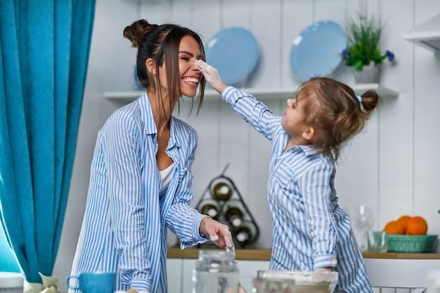 엄마와 딸은 밀가루로 부엌에서 놀고 있습니다. 소녀는 코를 닦고 웃는다.