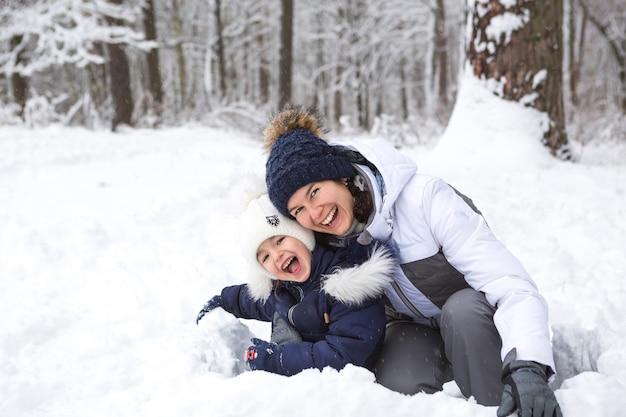 Мама и дочь играют в снежные игры, строят крепости, лепят снежки. зимние каникулы