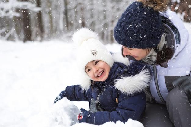 Мама и дочка играют в снежные игры, строят крепости, лепят снежки