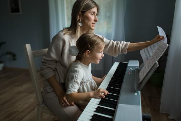 엄마와 딸이 집에서 신디사이저를 연주합니다. 집에서 신디사이저를 배우십시오. 고품질.