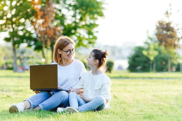 Мама и дочь играют в ноутбуке на открытом воздухе, смеются и наслаждаются летним солнцем на зеленой траве в парке, семья на открытом воздухе в парке