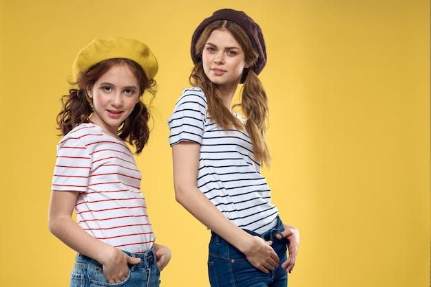 ママと娘が黄色の壁にポーズ